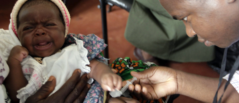 A child is given an injection as part of a malaria vaccine trial at a clinic in the Kenya coastal town of Kilifi, November 23, 2010. Malaria threatens half the people on the planet and kills around 800,000 people a year, many of them too young to have even learned to walk. The death rate has come down in the last decade, but full-scale eradication will cost billions and drag funds away from other equally, or possibly even more urgent health efforts. As governments in poor countries and donors from wealthy ones weigh up where to put their money, experts have begun a quiet but fundamental debate about whether wiping out malaria is realistic or even makes economic sense. Picture taken November 23, 2010. To match Special Report MALARIA/COST     REUTERS/Joseph Okanga (KENYA - Tags: BUSINESS HEALTH) - RTXVPMI