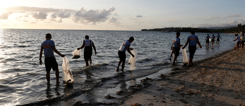 Policemen collect trash in the waters off the beach at the holiday island of Boracay during the first day of a temporary closure for tourists, in Philippines April 26, 2018. REUTERS/Erik De Castro - RC18B5D0F350