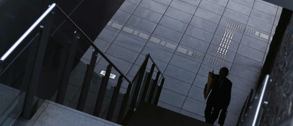 A man goes up the stairs at Tokyo's business district.