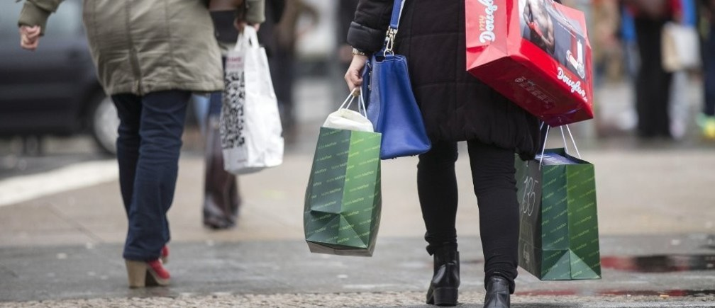 People carry bags outside a shopping mall on the last day of Christmas shopping in Berlin December 23, 2014.