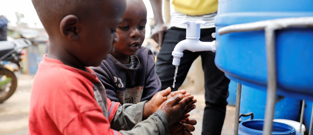 Children wash their hands against the spread of the coronavirus disease (COVID-19) at a hand washing station set up by community organisation Shining Hope for Communities (SHOFCO) in the Kibera slum in Nairobi, Kenya, March 18, 2020. REUTERS/Baz Ratner - RC2EMF9FM85S