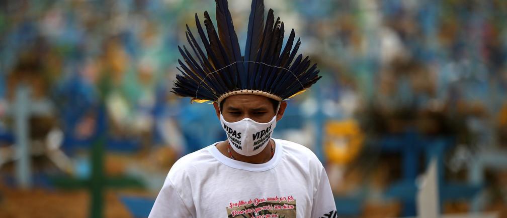 """El indígena Miqueias Moreira Kokama, lleva una máscara protectora con palabras que dicen: """"Las vidas de los indígenas importan"""", durante una visita a la tumba de su padre, el jefe indígena Messias Kokama, que falleció debido a la enfermedad coronavirus (COVID-19), en el cementerio de Parque Taruma en Manaus, Brasil, el 26 de mayo de 2020."""