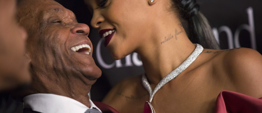 Singer Rihanna and her grandfather Lionel Braithwaite share a laugh at the First Annual Diamond Ball fundraising event at The Vineyard in Beverly Hills, California December 11, 2014. The event benefits the Clara Lionel Foundation (CLF).