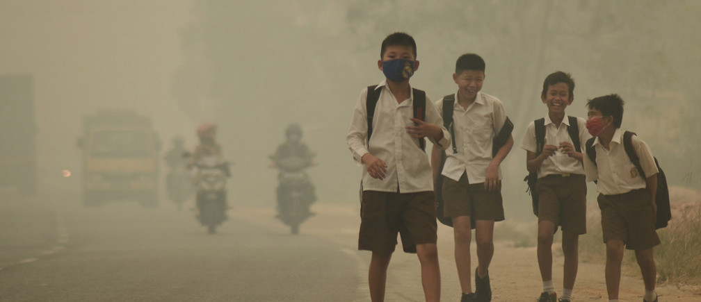 Students walk along a street as they are released from school to return home earlier due to the haze in Jambi, Indonesia's Jambi province, September 29, 2015 in this file picture taken by Antara Foto. Antara Foto/Wahdi Setiawan/via REUTERS/File Photo ATTENTION EDITORS - THIS IMAGE WAS PROVIDED BY A THIRD PARTY. FOR EDITORIAL USE ONLY. MANDATORY CREDIT. INDONESIA OUT. - S1BEUCIXHTAB