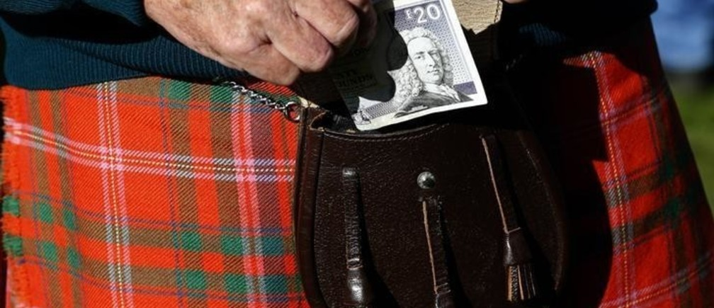 A man puts money in his sporran at the Birnam Highland Games in Scotland, August 30, 2014. Scotland will hold a referendum on independence on September 18. REUTERS/Russell Cheyne (BRITAIN - Tags: SOCIETY POLITICS)