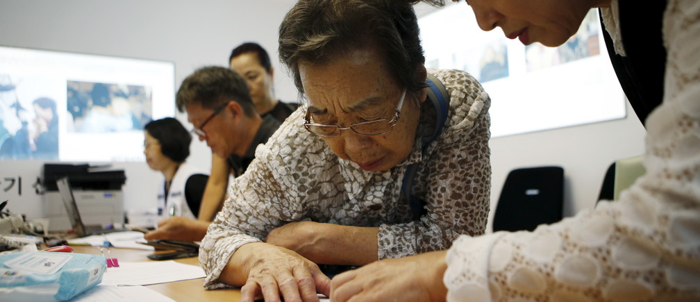 A woman who said she has family members living in North Korea gets help to prepare documents for reunion at the Red Cross building in Seoul, South Korea, September 8, 2015. Families torn apart by the Korean War six decades ago are to reunite briefly near the heavily fortified border of North and South Korea next month under a deal reached between the two sides on Tuesday, according to a statement from the South.  REUTERS/Kim Hong-Ji - RTX1RKLB