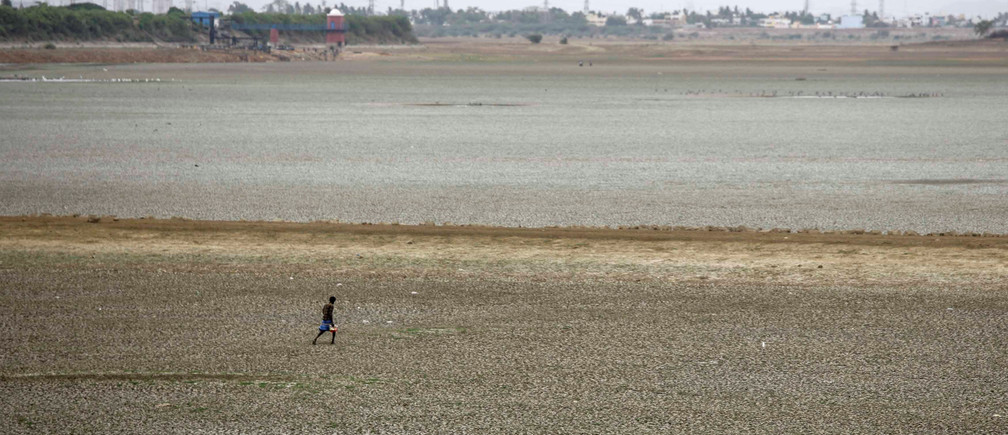 A man walks through the dried-up Puzhal reservoir, on the outskirts in Chennai, India, June 20, 2019. REUTERS/P. Ravikumar - RC1C4DEC0FC0