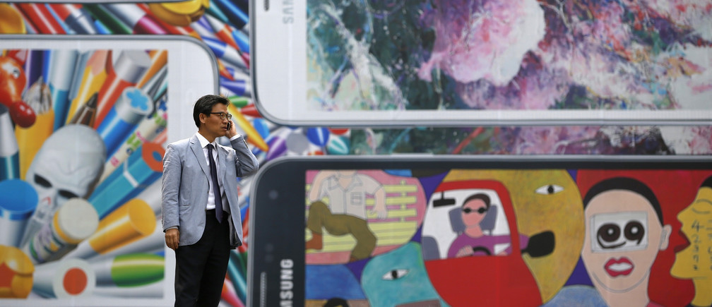 A man uses his mobile phone in front of a giant advertisement promoting Samsung Electronics' new Galaxy S5 smartphone, at an art hall in central Seoul April 15, 2014. Samsung Electronics Co Ltd's new Galaxy S5 smartphone should outsell its predecessor and defy predictions that the South Korean titan's latest model will struggle in a tough market for high-end handsets, Yoon Han-kil, senior vice president of Samsung's product strategy team, told Reuters in an interview. Picture taken on April 15, 2014. To match Interview SAMSUNG-ELEC-SALES/  REUTERS/Kim Hong-Ji (SOUTH KOREA - Tags: BUSINESS SCIENCE TECHNOLOGY TELECOMS) - GM1EA4G0OFM01