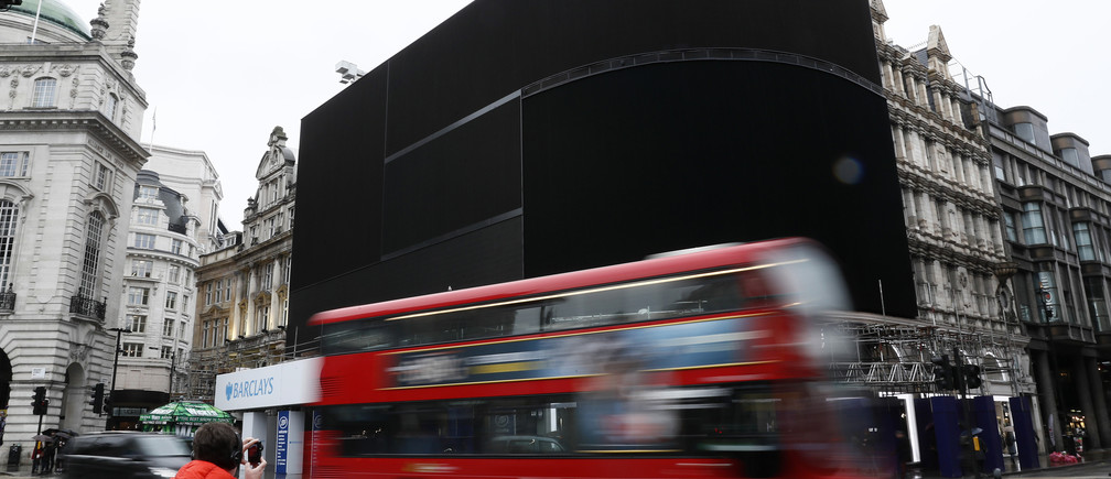 A double decker bus passes the advertisement boards at Piccadilly Circus which have been switched off prior to being replaced with more modern screens, in central London, Britain January 16, 2017. REUTERS/Stefan Wermuth, - LR1ED1G11CK5E