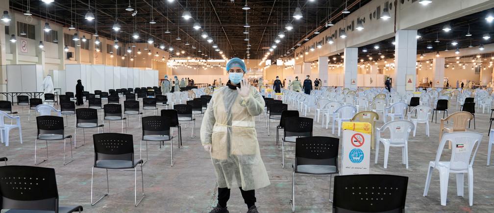 Un voluntario, que dirige a los visitantes en un centro de pruebas de coronavirus, hace gestos en el recinto de la Feria Internacional de Kuwait en Mishref (Kuwait) el 18 de marzo de 2020.