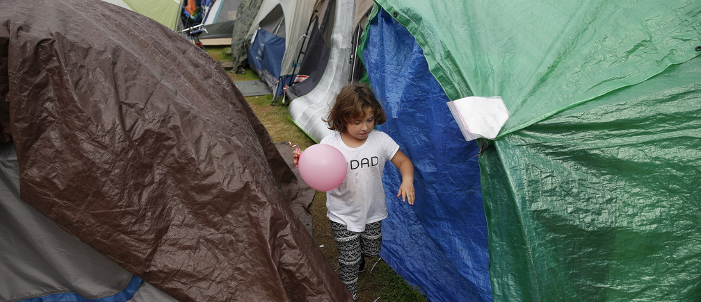 "Emma Savage, 6, runs with a balloon between tents at SHARE/WHEEL Tent City 3 outside Seattle, Washington October 13, 2015. SHARE and WHEEL describe themselves as self-organised, democratic organisations of homeless and formally homeless people which run several self-managed tent cities. REUTERS/Shannon Stapleton PICTURE 23 OF 35 - SEARCH ""STAPLETON TENTS"" FOR ALL IMAGES - RTX1Z3JW"