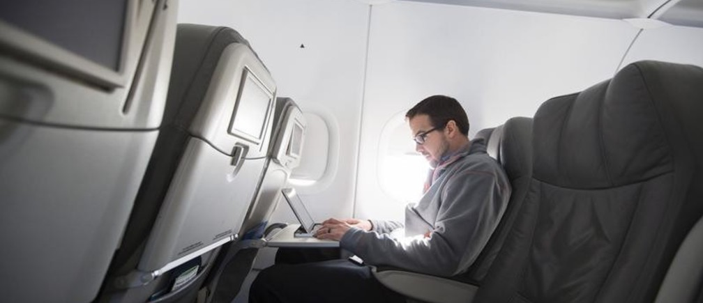 A man uses his laptop to test a new high speed inflight Internet service named Fli-Fi while on a special JetBlue media flight out of John F. Kennedy International Airport in New York in this December 11, 2013 file picture.        REUTERS/Lucas Jackson/Files - GF10000375003