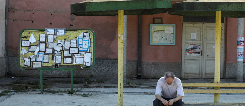 """Death notices are seen on a notice board as a man sits at a bus station in the village of Kalna, near the south-eastern town of Knjazevac, Serbia, August 16, 2016.  REUTERS/Marko Djurica        SEARCH """"DEPOPULATION"""" FOR THIS STORY. SEARCH """"WIDER IMAGE"""" FOR ALL STORIES. - RC19D6A29D00"""