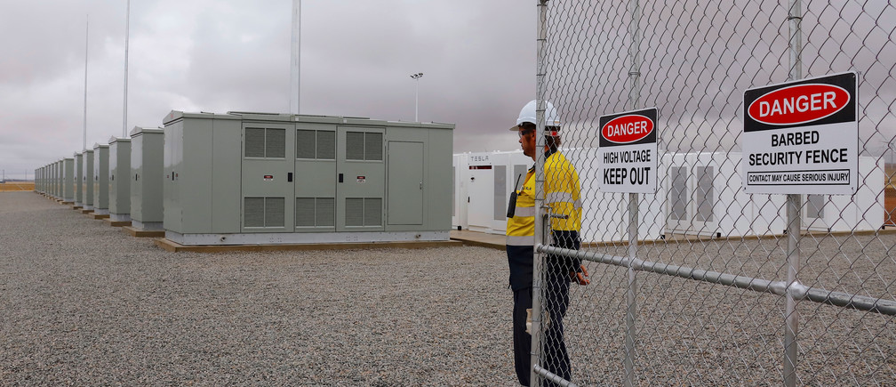 A worker stands at the main gate for the compound housing the Hornsdale Power Reserve, featuring the world's largest lithium ion battery made by Tesla, during the official launch near the South Australian town of Jamestown, in Australia, December 1, 2017.      REUTERS/David Gray - RC1642836A20