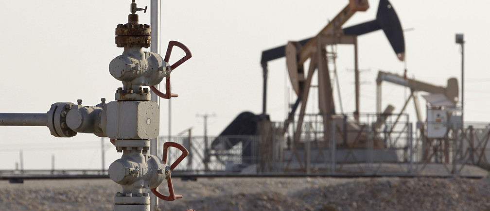 The first oil well of the region (L), which was discovered in 1931, is seen with new and advanced oil pumping machines in the background in Sakir, south of Manama, October 11, 2014.
