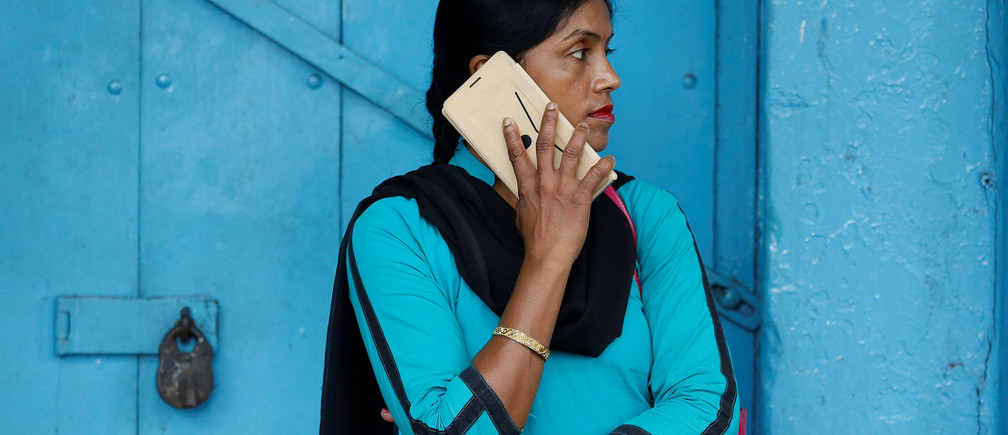 A woman talks on her mobile phone on a pavement in Kolkata, India July 5, 2017. REUTERS/Rupak De Chowdhuri - RC11E9915720