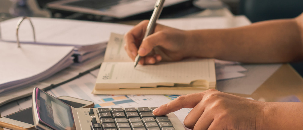 Man hand using a financial calculator with writing make note and Financial data analyzing on desk at home