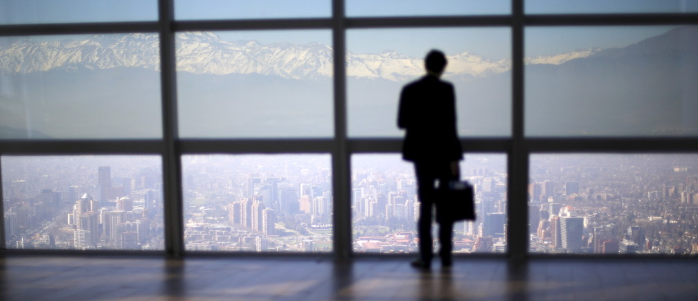 A man looks out to the Los Andes mountain range next to the city from a rooftop of a commercial center in a business district in Santiago, Chile, September 3, 2015.  REUTERS/Ivan Alvarado      TPX IMAGES OF THE DAY           TPX IMAGES OF THE DAY      - RTX1QYUU