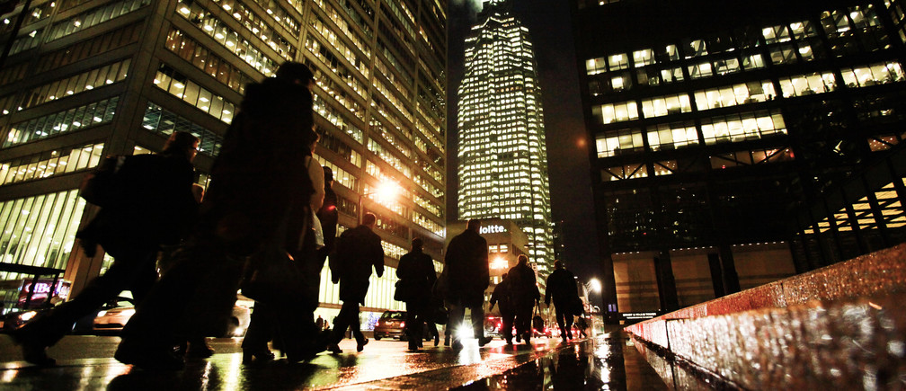 People walk down Bay St in the heart of the financial district in downtown Toronto.