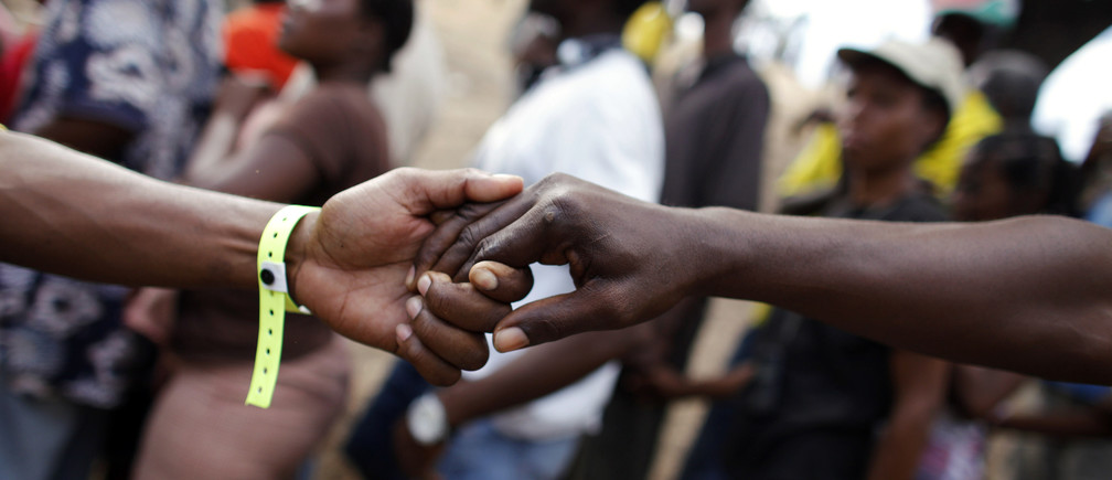 Haitian volunteers hold hands in a human chain to form a queue for people to line up during a food distribution by the U.S. forces in Port-au-Prince, January 27, 2010.