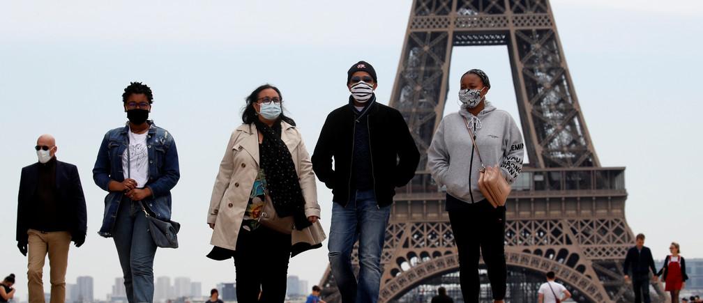 Personas con máscaras faciales caminan en la plaza de Trocadero, cerca de la Torre Eiffel, mientras Francia comenzaba a poner fin gradualmente a un bloqueo nacional debido a la enfermedad coronavirus (COVID-19) en París, Francia, el 16 de mayo de 2020.