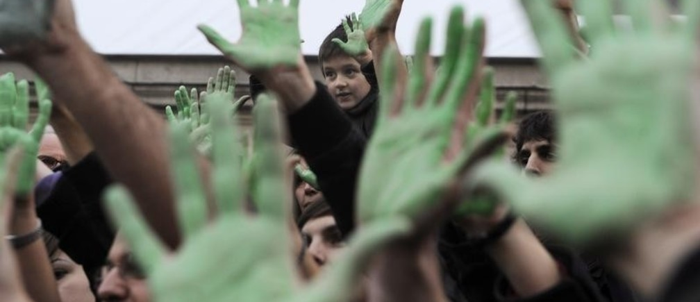 Demonstrators hold up painted green hands during a protest organised by the Coalicion Clima against climate change at the Reina Sofia Square in Madrid December 12, 2009. REUTERS/Vincent West (SPAIN - Tags: CIVIL UNREST POLITICS ENVIRONMENT IMAGES OF THE DAY) - RTXRS6M