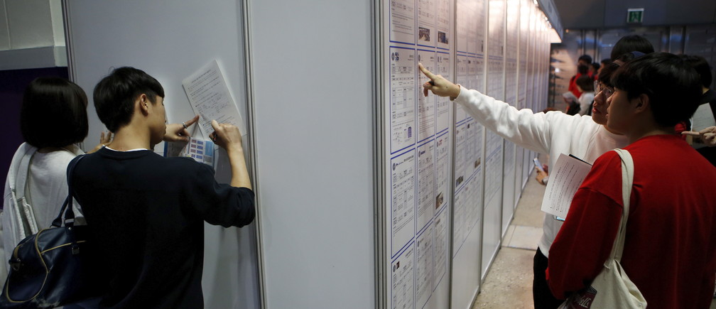 University students (R) look at recruiting information as others write on documents at an employment fair in Seoul, South Korea, September 23, 2015.