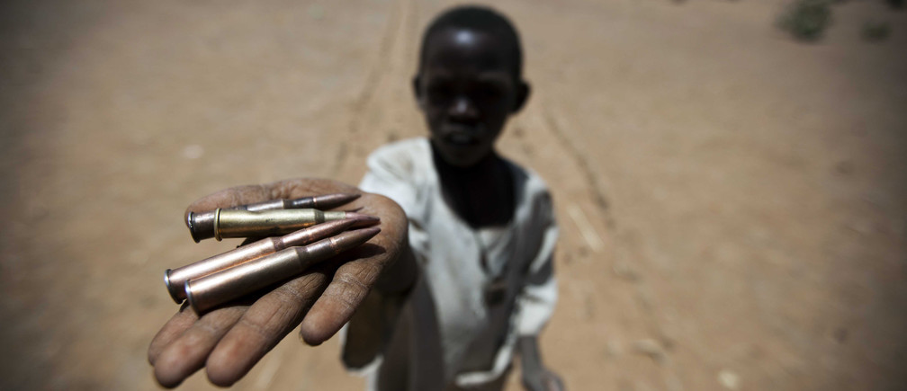 A child holds bullets picked from the ground, in Rounyn, a village located about 15 km north of Shangil Tobaya, North Darfur March 27, 2011.