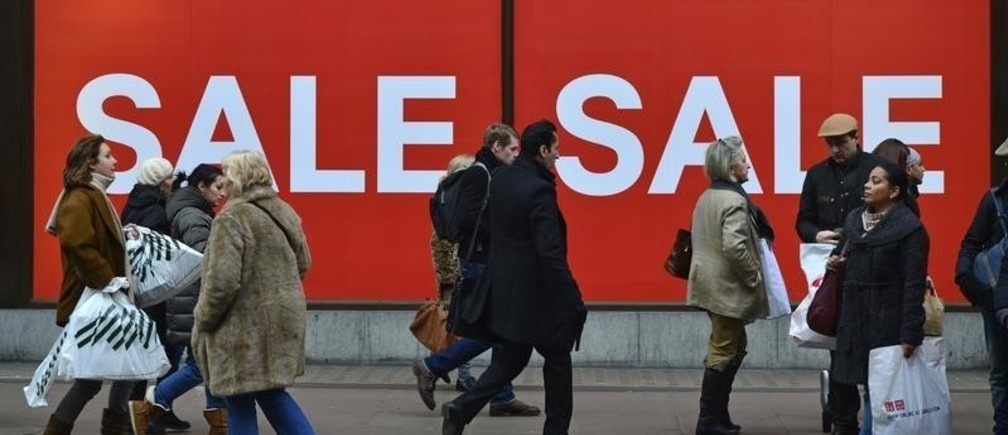 Pedestrains walk past a shop sale sign in Oxford Street, central London December 13, 2012. REUTERS/Toby Melville  (BRITAIN - Tags: BUSINESS EMPLOYMENT) - RTR3BJ6W