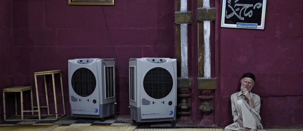 A man sits beside portable air coolers at a mosque inside the shrine of Sufi Saint Nizamuddin Auliya after evening prayers in New Delhi May 30, 2013.