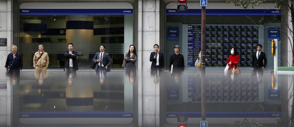 Pedestrians standing in front of an electronic board displaying various stock prices outside a brokerage are reflected in a polished stone surface, in Tokyo October 23, 2013.