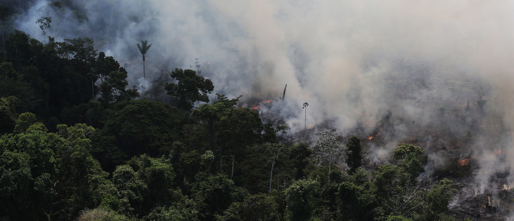 An aerial view of a tract of Amazon jungle burning as it is being cleared by loggers and farmers near the city of Novo Progresso, Para state, September 23, 2013. The Amazon rainforest is being eaten away at by deforestation, much of which takes place as areas are burnt by large fires to clear land for agriculture. Initial data from Brazil's space agency suggests that destruction of the vast rainforest - the largest in the world - spiked by more than a third over the past year, wiping out an area more than twice the size of the city of Los Angeles. If the figures are borne out by follow-up data, they would confirm fears of scientists and environmental activists who warn that farming, mining and Amazon infrastructure projects, coupled with changes to Brazil's long-standing environmental policies, are reversing progress made against deforestation. Environmental issues will be under the spotlight as a United Nations Climate Change Conference opens in Warsaw, Poland on November 11. Picture taken on September 23, 2013.  REUTERS/Nacho Doce (BRAZIL  - Tags: ENVIRONMENT POLITICS AGRICULTURE)   - RTX159YJ