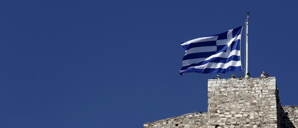 Tourists stand under a Greek national flag atop the Acropolis hill in Athens, June 14, 2015. Greek Prime Minister Alexis Tsipras said he was willing to accept unpalatable compromises to secure a deal with international creditors provided he gets debt relief in return, something that Germany refuses to countenance.    REUTERS/Kostas Tsironis - RTX1GEZV