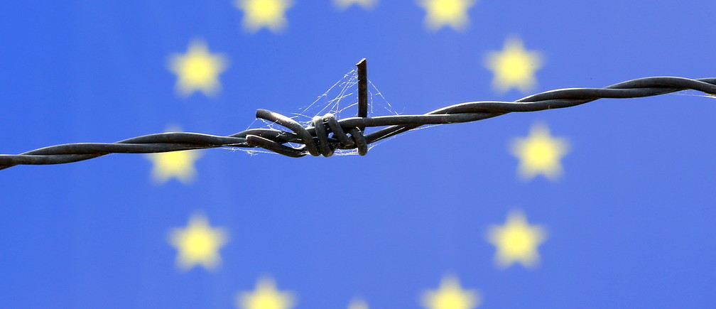 A barbed wire is seen in front of European Union flag in an immigration reception centre in Bicske, Hungary June 25, 2015. Austria threatened to reimpose controls on its Hungarian border and Britain considered adding security around the French port of Calais on Wednesday as divided EU leaders prepared to debate how to stem a flood of desperate migrants. Austria's warning about reinstating checks on its passport-free border with Hungary follows a refusal by Budapest to take in asylum seekers sent back to it by other member states under EU rules. Hungary says it no longer has the means to deal with a sharp increase in people streaming over its Balkan border - many from the Middle East, including via crisis-wracked Greece. REUTERS/Laszlo Balogh  - GF10000138877