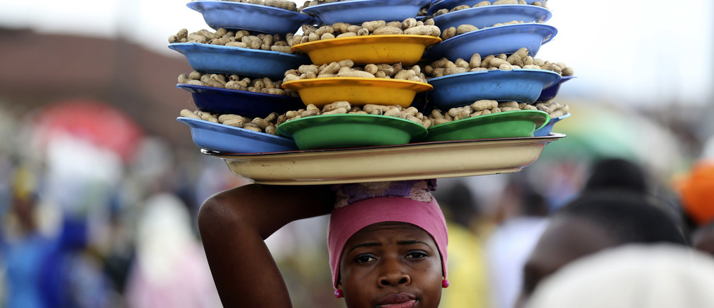 A girl hawks groundnuts arranged on a tray along a road in Nigeria's southwest city of Osogbo, August 11, 2014.REUTERS/Akintunde Akinleye(NIGERIA - Tags: SOCIETY) - GM1EA8C0C5I01