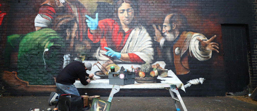 Artist Lionel Stanhope paints a mural in Ladywell depicting the Supper at Emmaus by Caravaggio with added protective gloves, following the outbreak of the coronavirus disease (COVID-19), London, Britain, May 5, 2020. REUTERS/Hannah McKay - RC2AIG94UANW