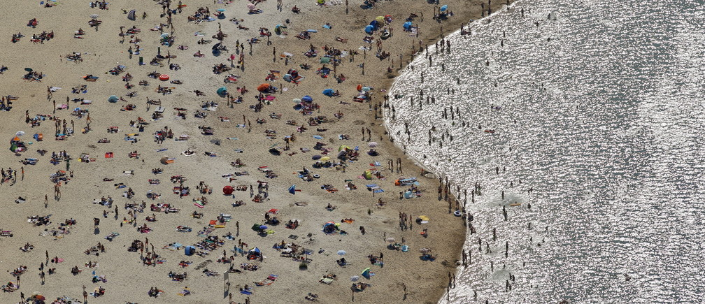 An aerial view shows people cooling off at a beach on the shores of the Silbersee lake on a hot summer day in Haltern, Germany, July 1, 2015. A widespread, long-lasting heatwave will affect much of France, Britain, Belgium, the Netherlands and western Germany. Forecast highs on Wednesday could reach 35 degrees Celsius (95 degrees Fahrenheit). REUTERS/Ina Fassbender - RTX1IN7W