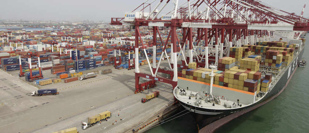 Trucks unload shipping containers from a cargo ship at Qingdao port in Qingdao, Shandong province September 2, 2011.