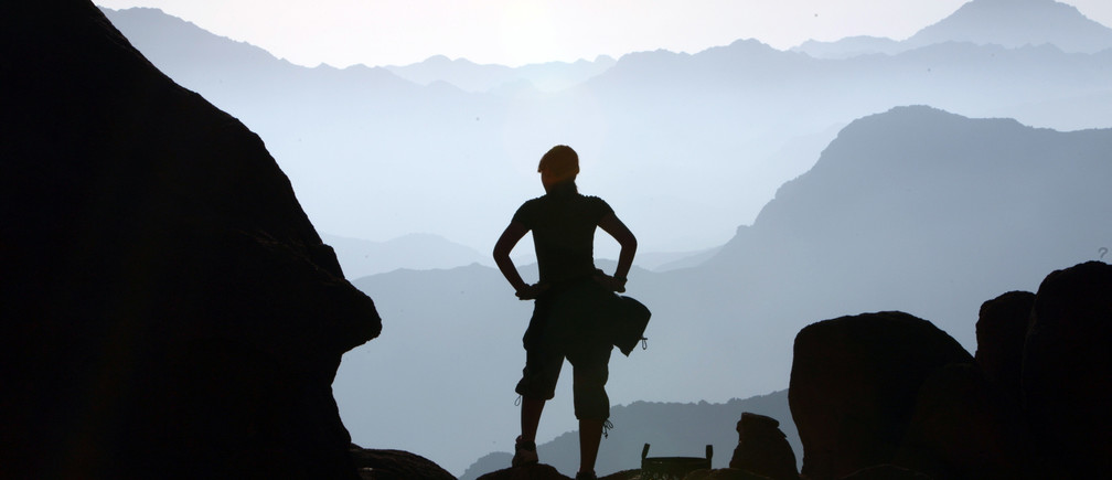 A visitor watches the sunrise at the summit of Mount Moses in the Sinai Peninsula August 10, 2009.