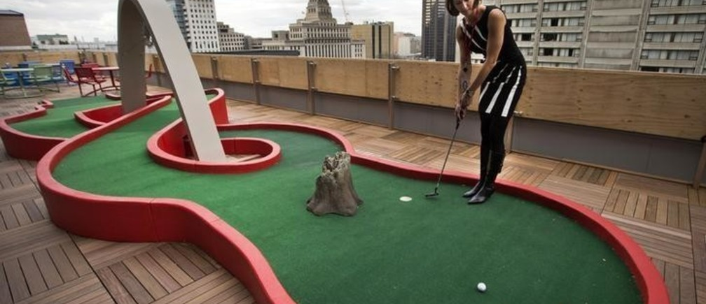 Google employee Andrea Janus demonstrates the use of the mini-putt green on the balcony at the new Google office in Toronto, November 13, 2012.    REUTERS/Mark Blinch (CANADA - Tags: SCIENCE TECHNOLOGY BUSINESS)