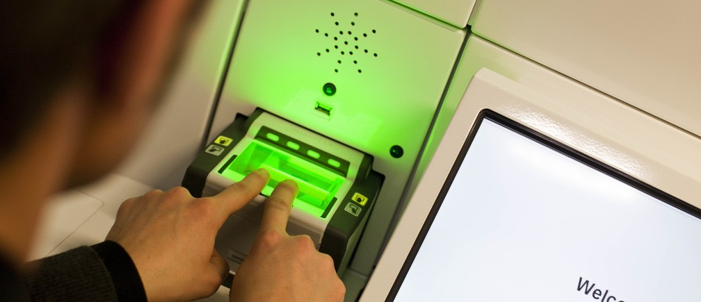 A man demonstrates the issuing of the new Swiss biometric passport at the Office of Passport Services in Zurich, January 26, 2010.