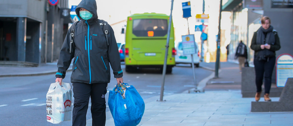 A man wearing a protective mask carries shopping bags as he walks on the streets of Oslo following an outbreak of the coronavirus disease (COVID-19), in Oslo, Norway March 13, 2020.