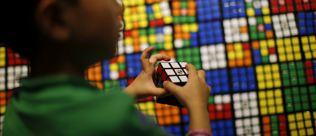 A boy plays with the Rubik's cube during an event to mark the 40th anniversary of the puzzle toy at the Liberty Science Center in Jersey City, New Jersey, April 26, 2014. REUTERS/Eduardo Munoz (UNITED STATES - Tags: SOCIETY ANNIVERSARY) - GM1EA4R0B2Z01