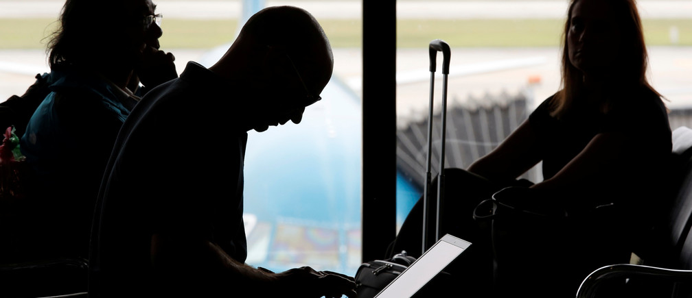 A man (C) works on a laptop at the airport in Hanoi, Vietnam October 18, 2017. REUTERS/Kham - RC11E49AE420