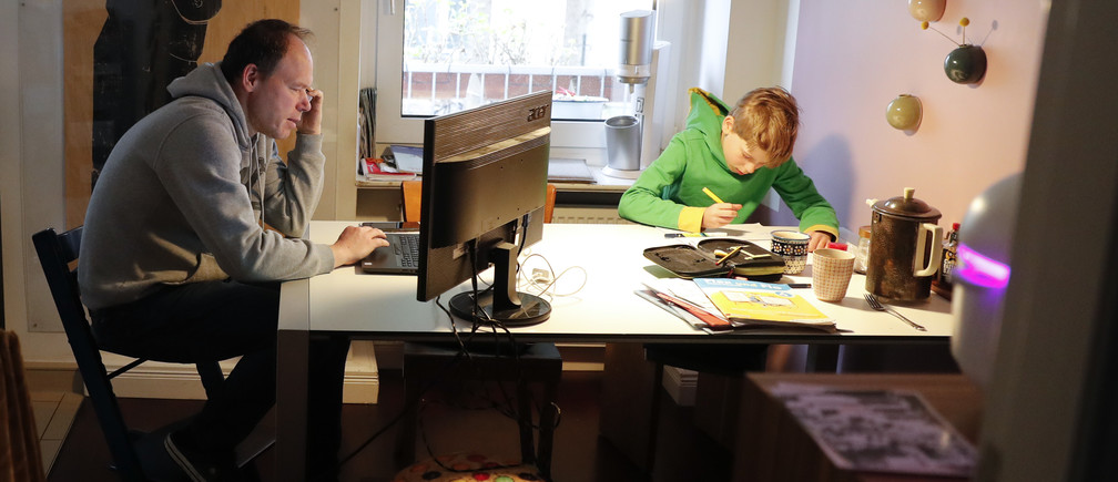 Holger Frohnmeyer, working from home, studies with his son Rasmus during the spread of coronavirus disease (COVID-19) in Berlin, Germany, March 19, 2020. REUTERS/Fabrizio Bensch - UP1EG3J0RUC51