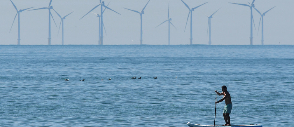 A man paddle boards, with an off-shore wind farm seen in the English Channel behind, during hot weather at Brighton in southern Britain, August 3, 2018. REUTERS/Toby Melville      TPX IMAGES OF THE DAY - RC11BA0ACF10