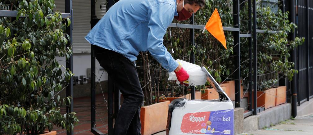 Un hombre con una máscara facial pone un paquete dentro de un robot de reparto de la compañía colombiana Rappi, en medio del brote de la enfermedad coronavirus (COVID-19) en Medellín, Colombia, el 17 de abril de 2020.