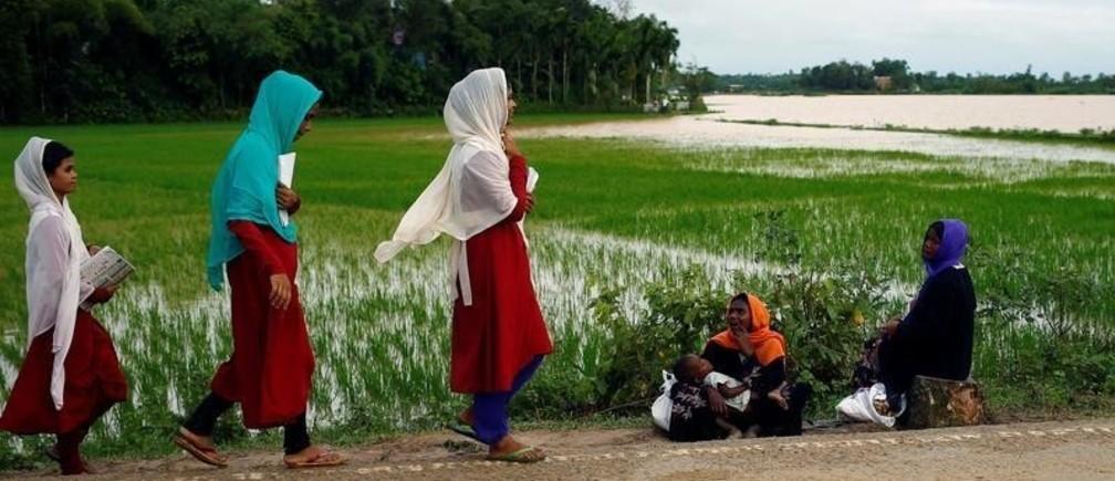 Rohingya refugee women sit on the roadside while local school girl pass by them near Balukhali Makeshift Camp in Cox's Bazar, Bangladesh