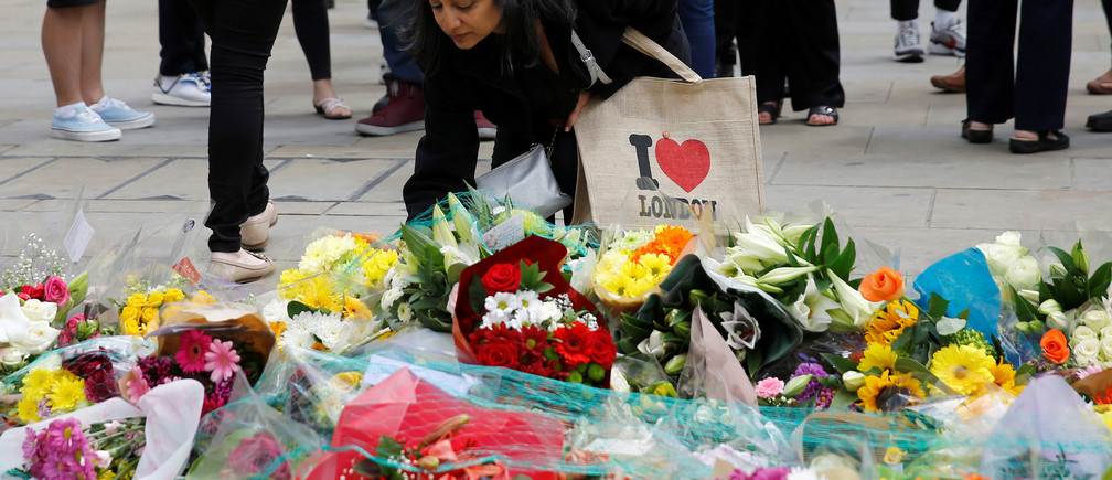 A woman leaves flowers near the scene of the attack at London Bridge and Borough Market in central London, Britain June 7, 2017. REUTERS/Stefan Wermuth - RC1CCDF36230