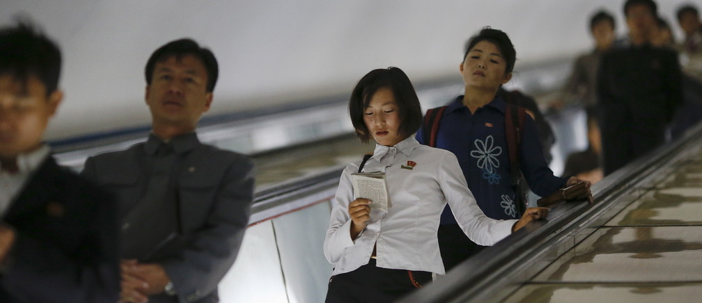 A woman reads a book as commuters make their way through a subway station in Pyongyang, North Korea October 9, 2015. Picture taken October 9, 2015. To match Insight NORTHKOREA-CHANGE/     REUTERS/Damir Sagolj - GF20000035870
